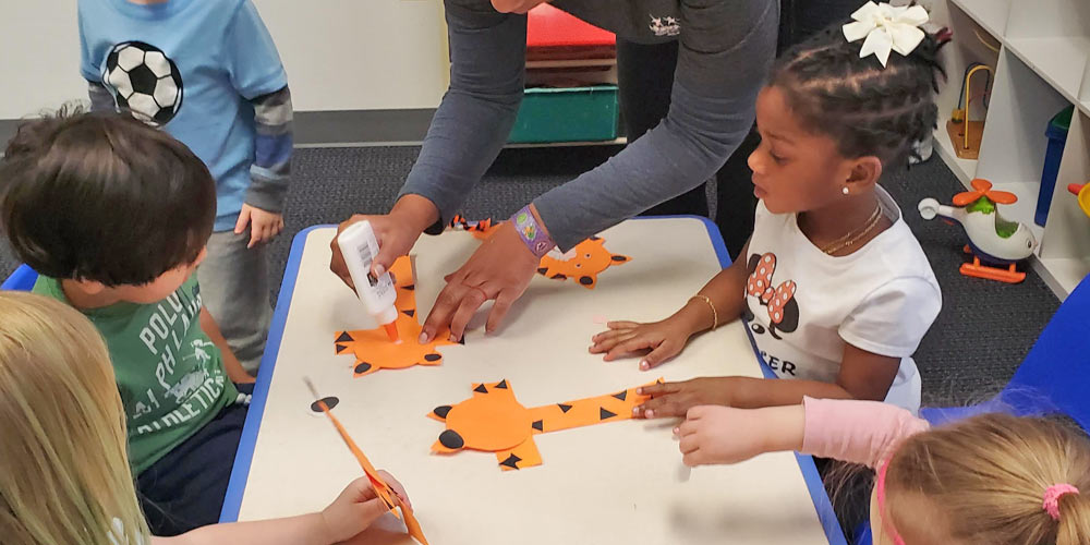 Teacher assists students with craft activity